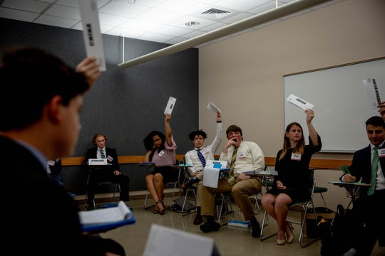 Students playing the roles of United Nations Security Council members raise their country labels to vote at the Southwest Florida Model United Nations Conference held at Florida Gulf Coast University on Thursday, March 7, 2019.