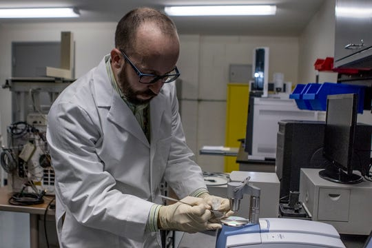 Mark Hiatt places a caffeine standard on the FTIR machine which uses infrared light to help identify what compounds are in any given substance.