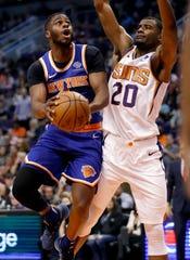 New York Knicks guard Emmanuel Mudiay shoots around Phoenix Suns forward Josh Jackson (20) during the first half of an NBA basketball game Wednesday, March 6, 2019, in Phoenix.