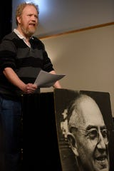 Don Zirilli reads a poem during a meeting of the Red Wheelbarrow Poets at the Williams Center for the Arts on Wednesday, March 6, 2019. A photo of William Carlos Williams is on display.