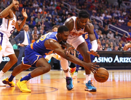 Mar 6, 2019; Phoenix, AZ, USA; Phoenix Suns center Deandre Ayton (right) and New York Knicks forward Noah Vonleh dive for a loose ball in the first half at Talking Stick Resort Arena.