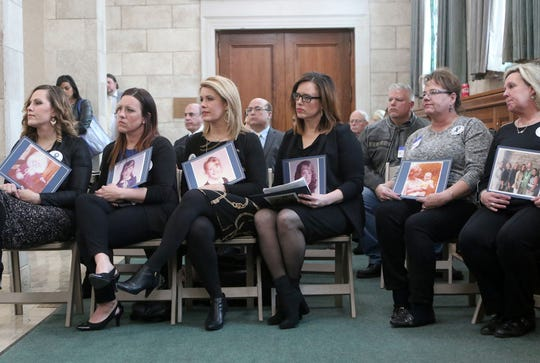The Fortney sisters hold childhood pictures of themselves while waiting to testify on the statute of limitations bill on March 7, 2019. Five of the Fortney siblings were abused by Father Augustine Giella, who worked for decades in New Jersey and Pennsylvania.