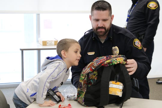 Bloomfield Police Lt. Randon Matthews examines Theodore Jones' backpack before the start of the department's Day in the Life of a Police Officer event on Thursday.