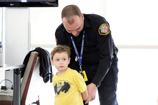 Bloomfield Police Department School Resource Officer Derek Booker demonstrates on James Young how officers place handcuffs on suspects Thursday during the department's Day in the Life of a Police Officer event.