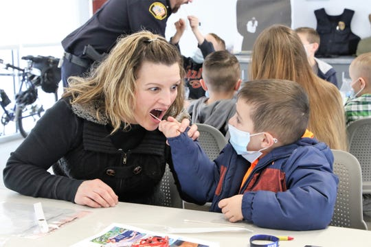 Kayde Marin, right, collects a DNA sample from Jenner Brynie, left, during the Bloomfield Police Department's Day in the Life of a Police Officer event Thursday at the police department building.