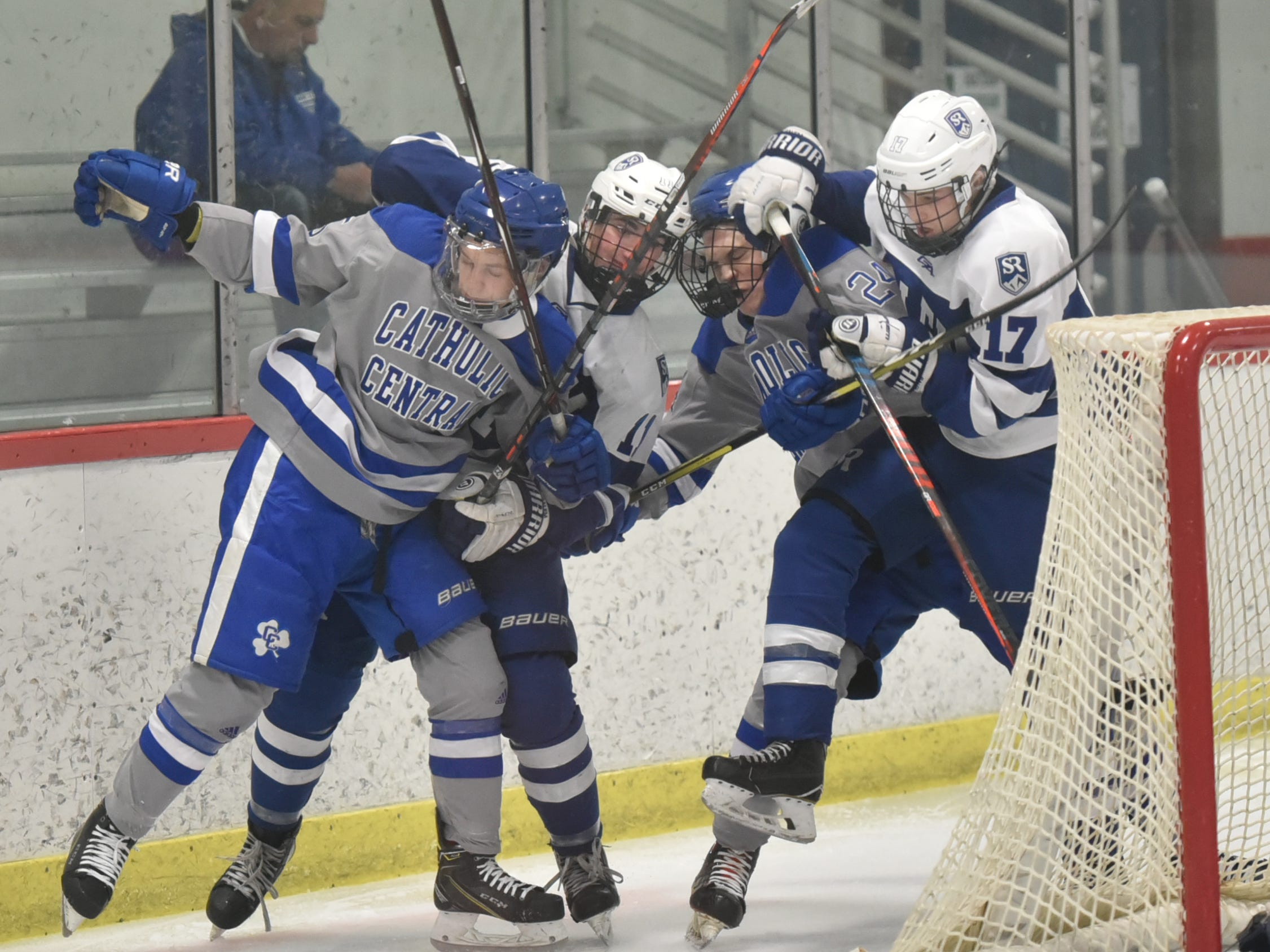 A pair of Salem High players greet their visitors from Detroit Catholic Central behind the Rock net - with some checking and grabbing.