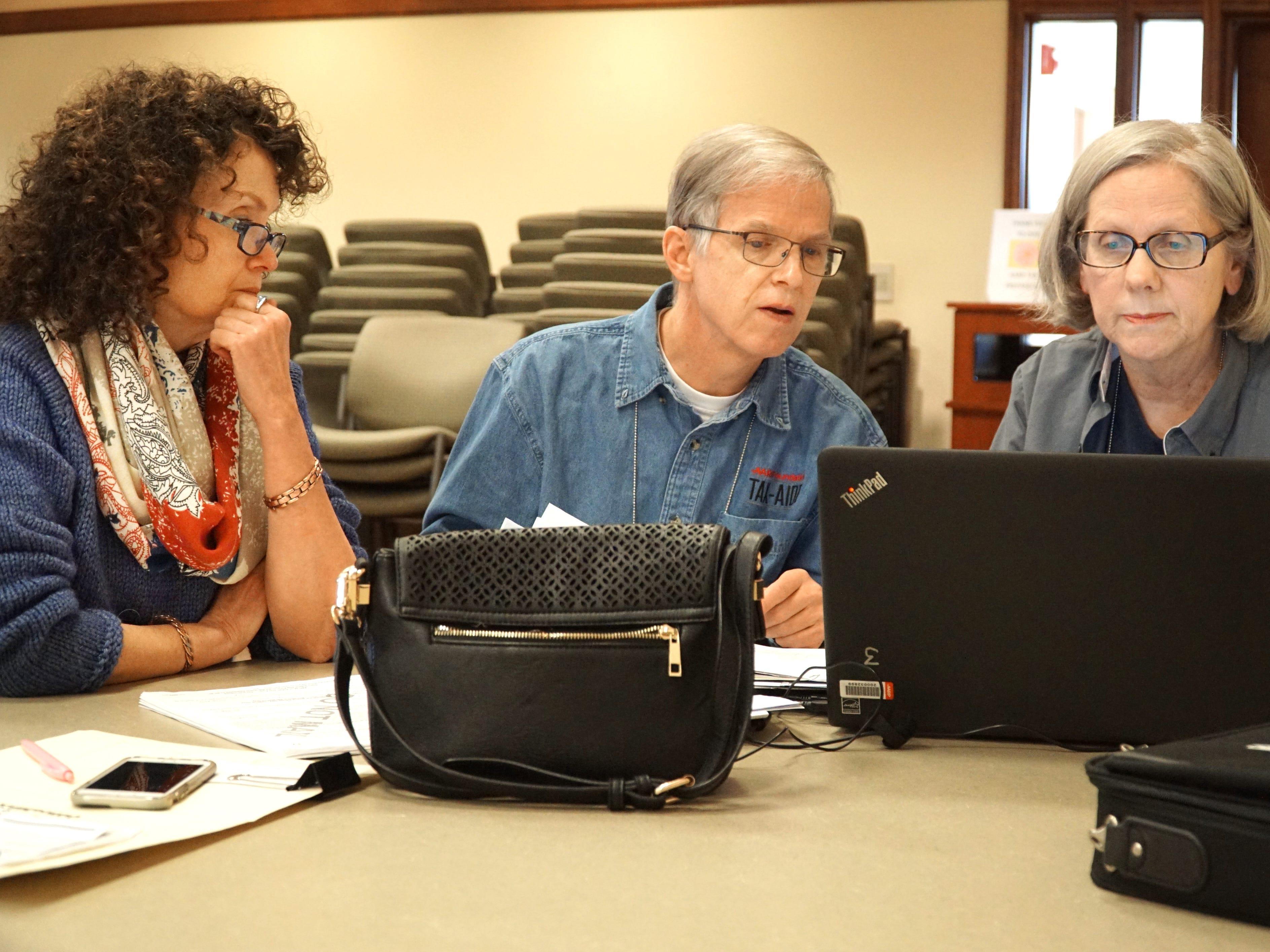 AARP volunteers Gene Wolbers and Diane Lahiff assist Linda Linder, left, in filing her 2018 taxes.
