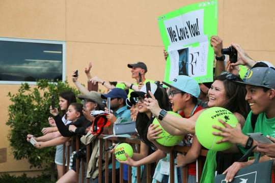 Fans wave to Roger Federer at the BNP Paribas Open, Indian Wells, Calif., Wednesday, March 6, 2019.