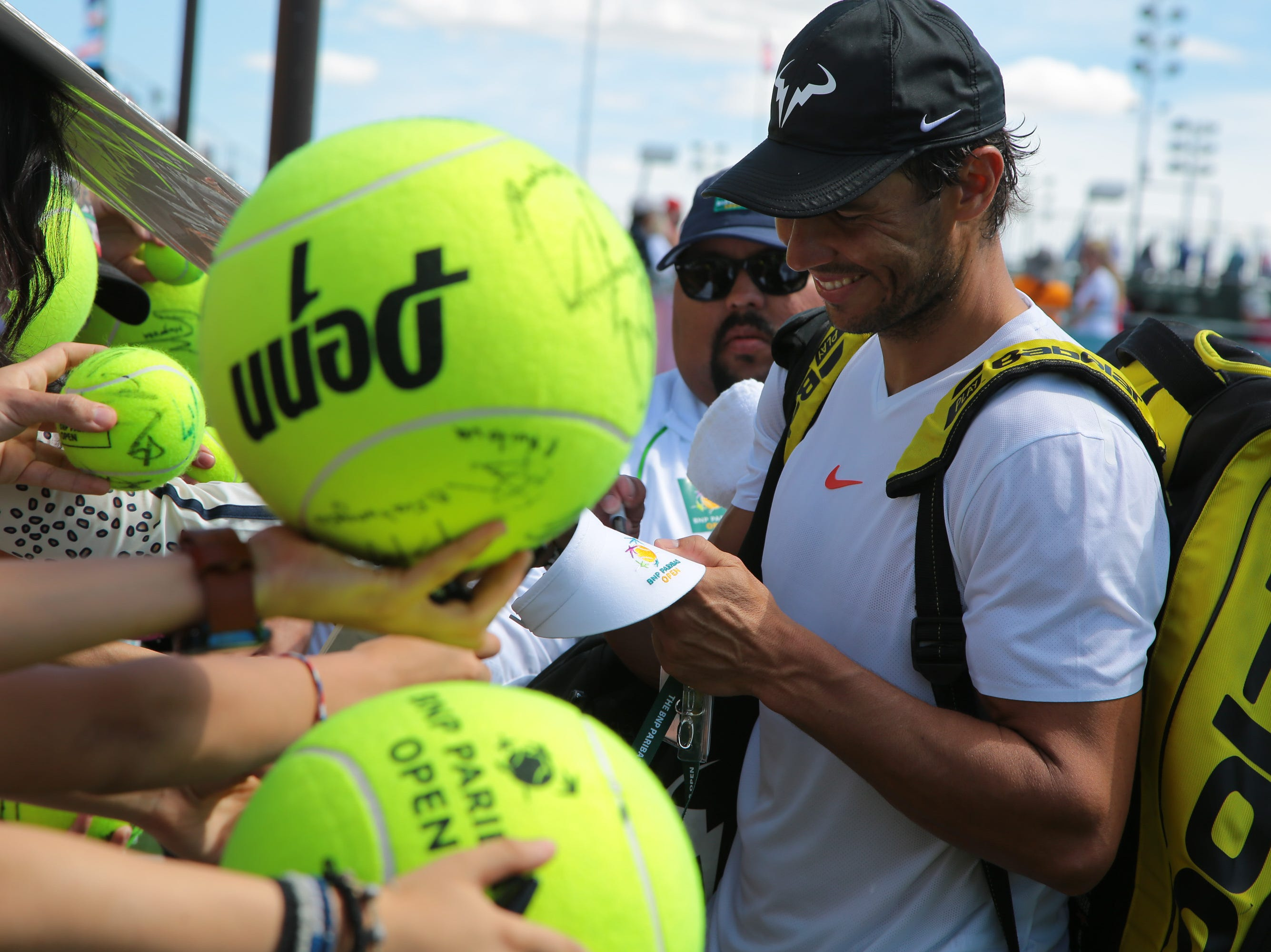 Rafael Nadal signs autographs for fans after practicing at the BNP Paribas Open, Indian Wells, Calif., Thursday, March 7, 2019.