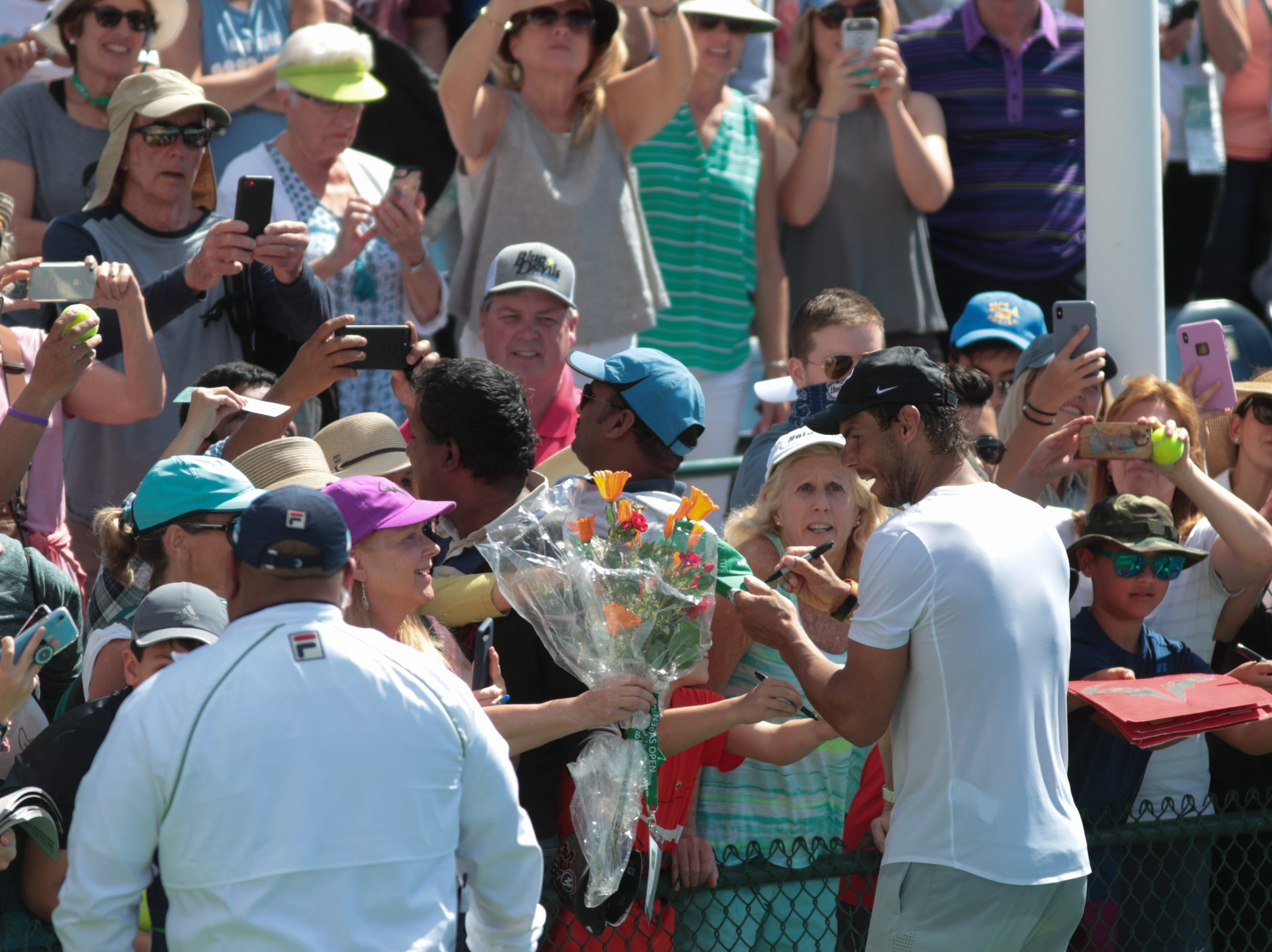 Rafael Nadal receives flowers from a fan after practicing at the BNP Paribas Open, Indian Wells, Calif., Thursday, March 7, 2019.
