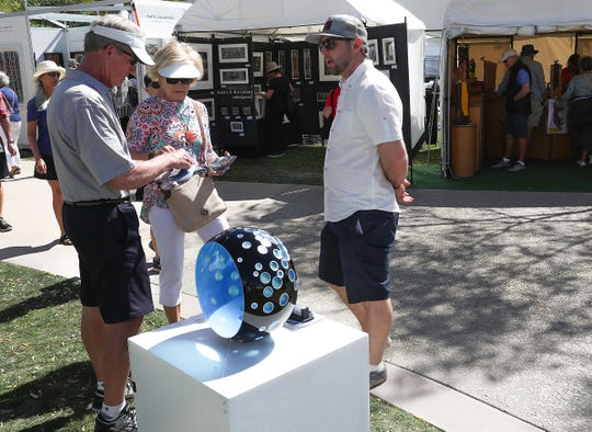 Artist Nick Leonoff, right, talks about his work with visitors to the La Quinta Arts Festival, March 7, 2019.