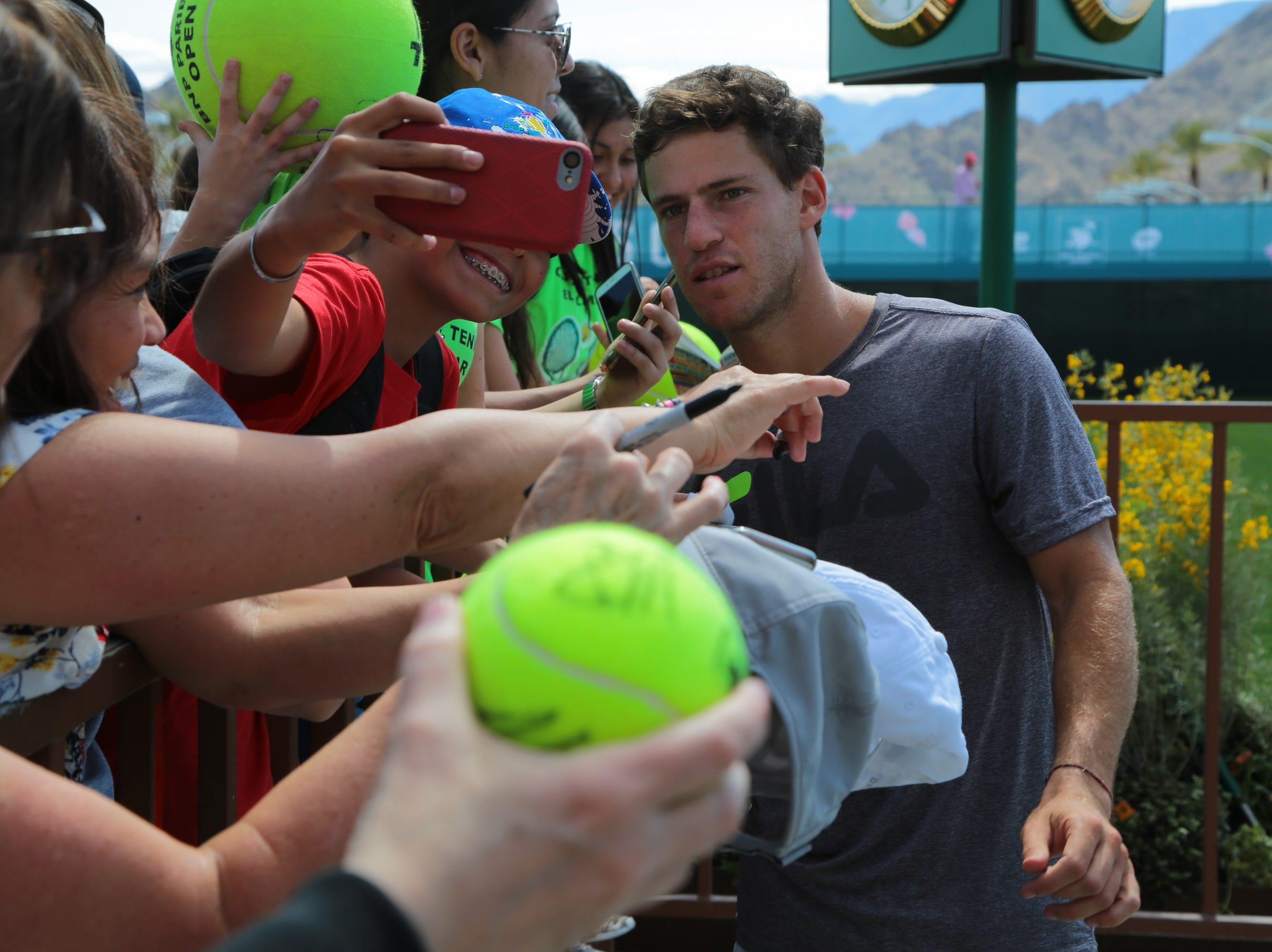 Diego Schwartzman takes a selfie with a fan after practicing at the BNP Paribas Open, Indian Wells, Calif., Thursday, March 7, 2019.