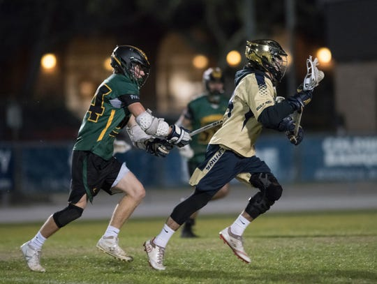 William Butler (24) tries to slow down TJ Caldwell (14) as he advances the ball during the Catholic vs. Gulf Breeze boys lacrosse game at Gulf Breeze High School on Wednesday, March 6, 2019.  The Dolphins won 11-9.