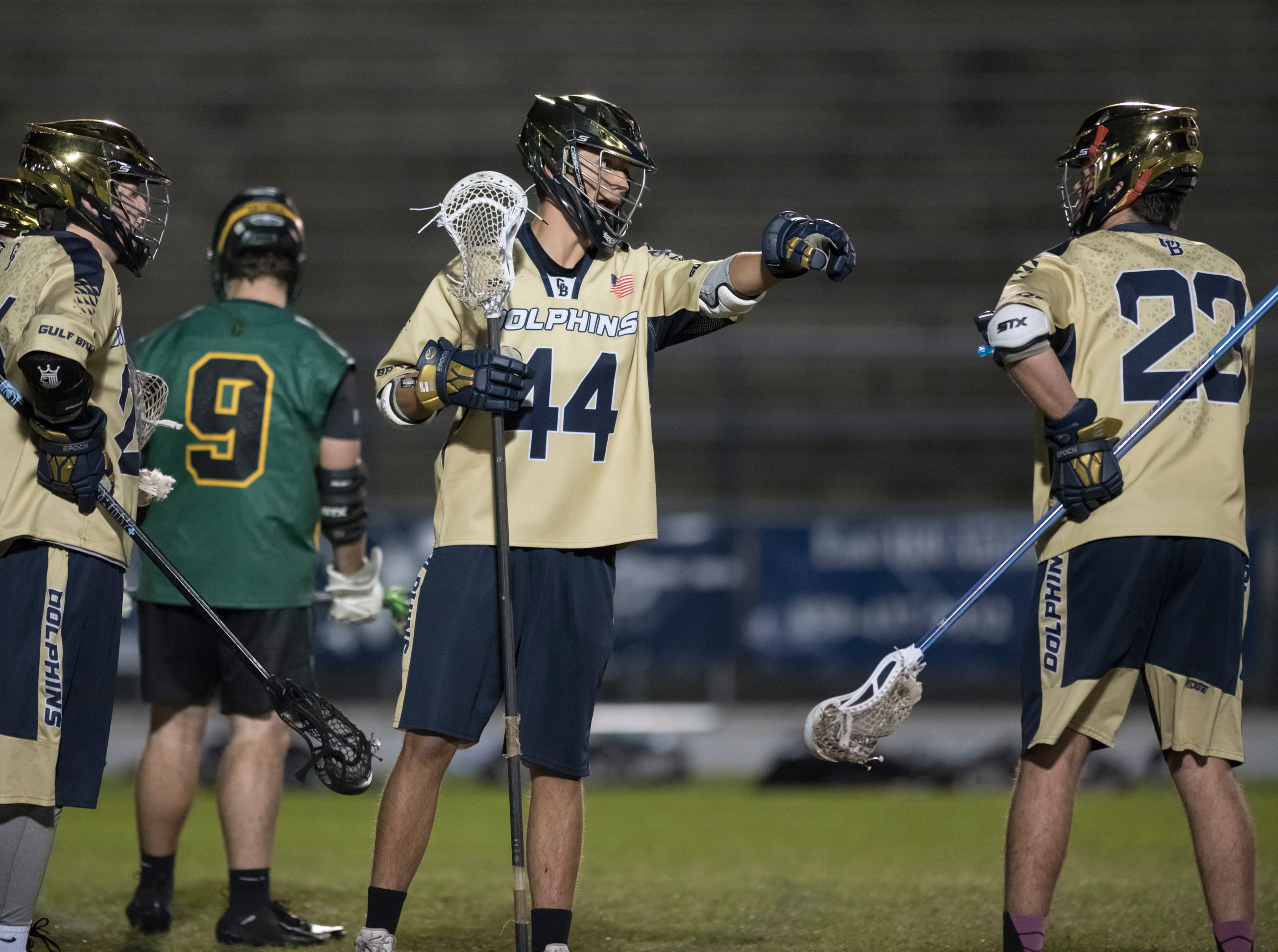 Eli Ryan (44) and teammates talk strategy after the Crusaders just took a 5-3 lead during the Catholic vs. Gulf Breeze boys lacrosse game at Gulf Breeze High School on Wednesday, March 6, 2019.