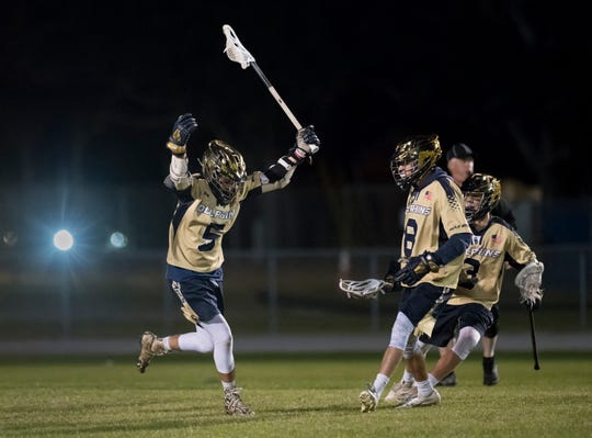 Ashton Marcum (5) celebrates scoring a goal and taking a 11-9 lead during the Catholic vs. Gulf Breeze boys lacrosse game at Gulf Breeze High School on Wednesday, March 6, 2019.