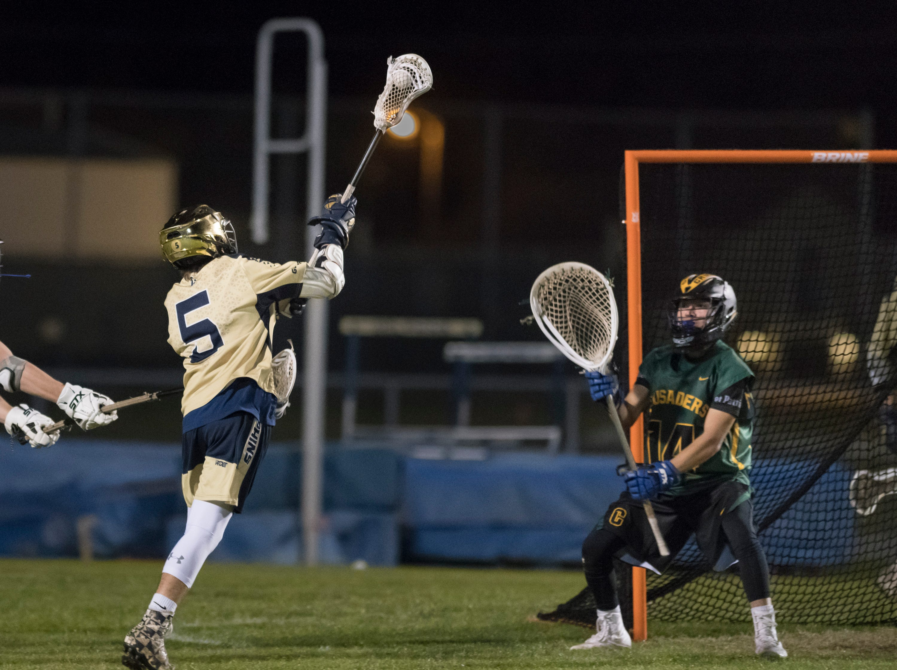 Ashton Marcum (5) shoots during the Catholic vs. Gulf Breeze boys lacrosse game at Gulf Breeze High School on Wednesday, March 6, 2019.