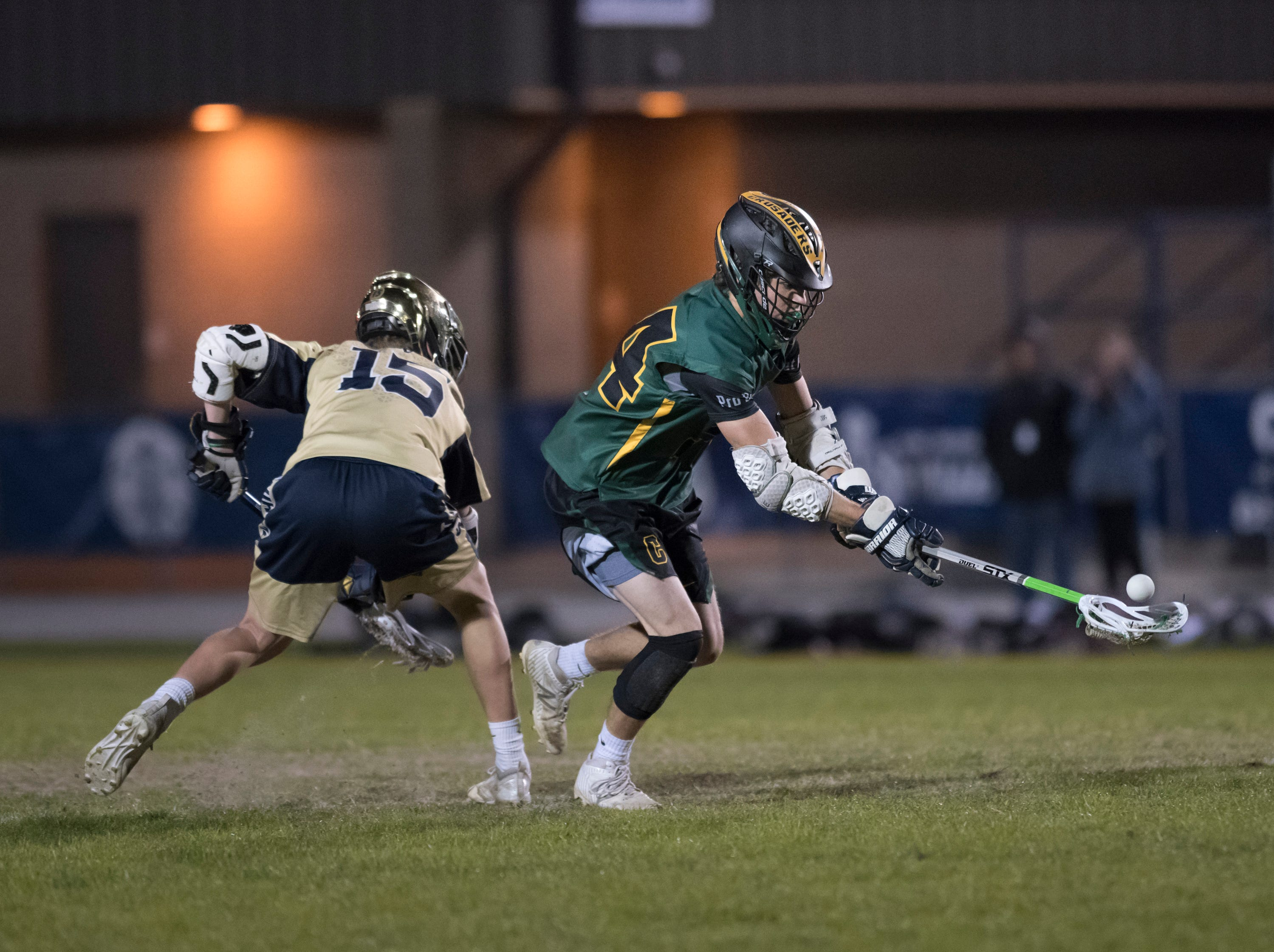 William Butler (24) scoops up the ball on a faceoff during the Catholic vs. Gulf Breeze boys lacrosse game at Gulf Breeze High School on Wednesday, March 6, 2019.