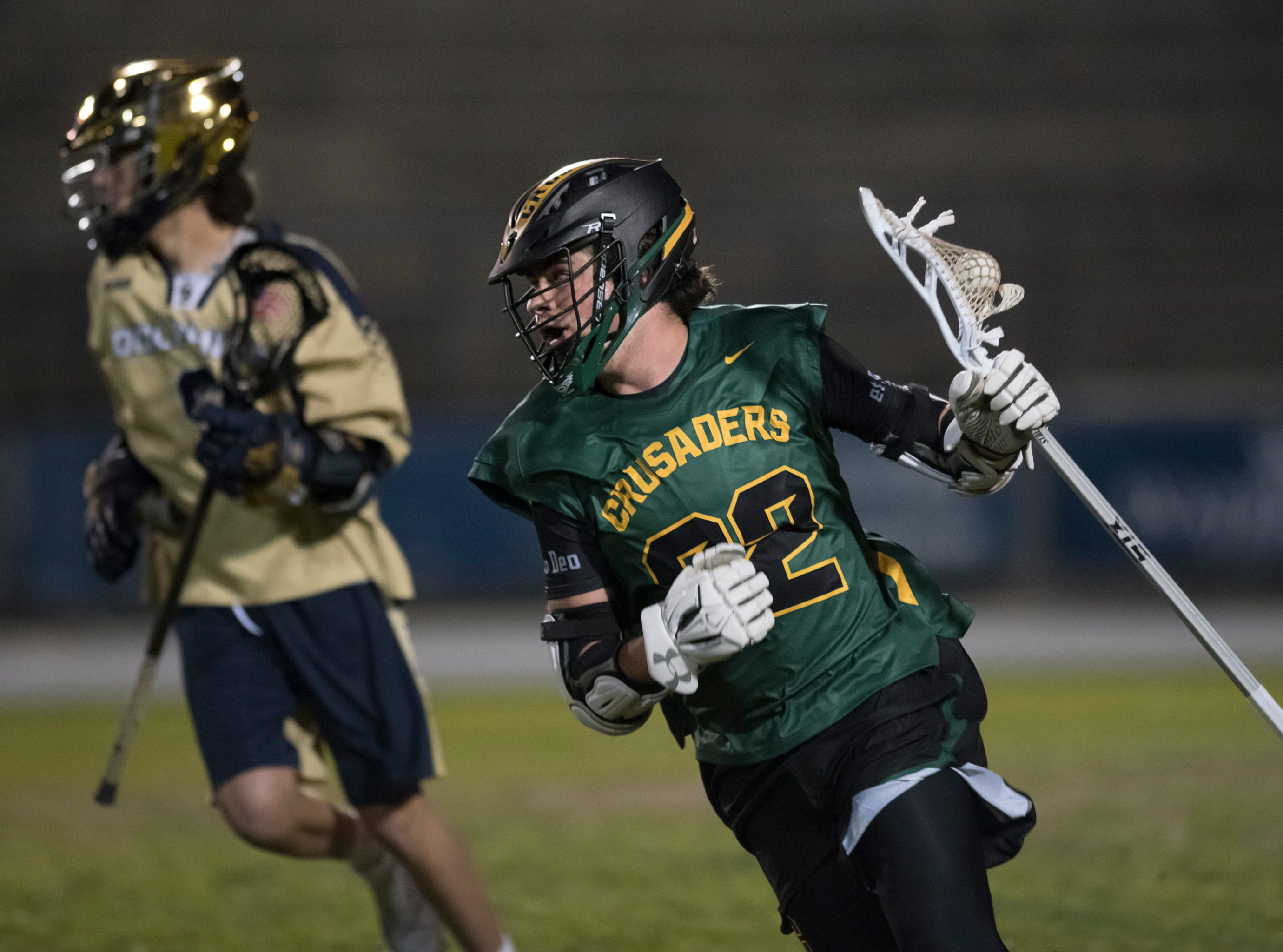 Ryan Campion (22) controls the ball during the Catholic vs. Gulf Breeze boys lacrosse game at Gulf Breeze High School on Wednesday, March 6, 2019.  The Dolphins won 11-9.