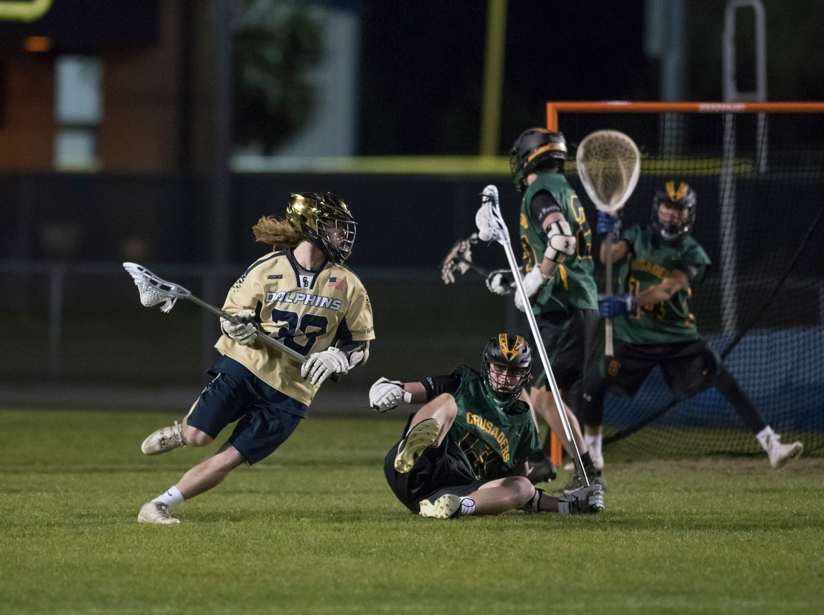 Kincade Essex (33) controls the ball during the Catholic vs. Gulf Breeze boys lacrosse game at Gulf Breeze High School on Wednesday, March 6, 2019.