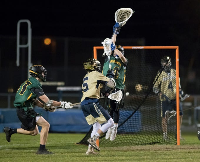 Ashton Marcum (5)'s shot gets past goalie Phillip Garcia (14) as the Dolphins take a 11-9 lead during the Catholic vs. Gulf Breeze boys lacrosse game at Gulf Breeze High School on Wednesday, March 6, 2019.