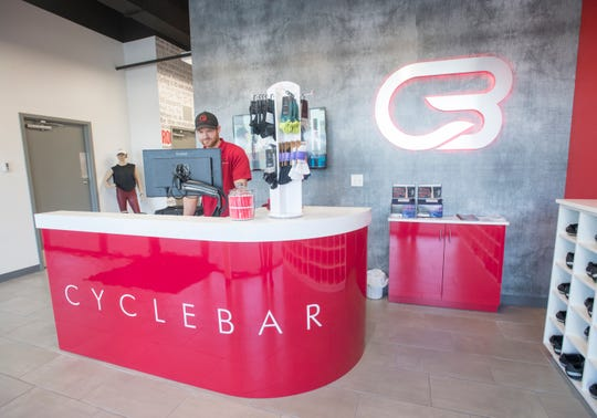General manager Chris Jones works the front desk at CycleBar on 9 Mile Road in Pensacola on Thursday, March 7, 2019.