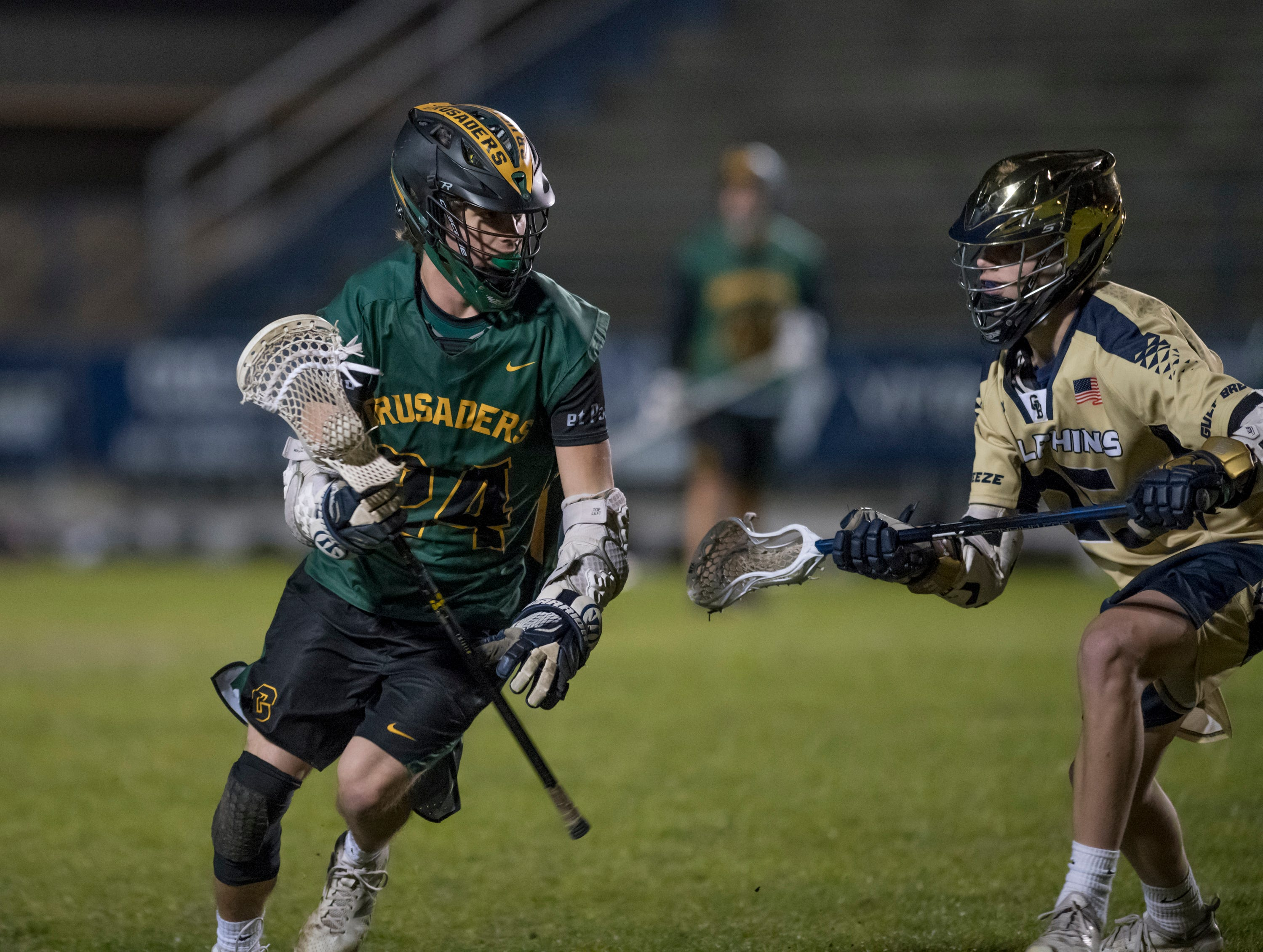 William Butler (24) controls the ball during the Catholic vs. Gulf Breeze boys lacrosse game at Gulf Breeze High School on Wednesday, March 6, 2019.