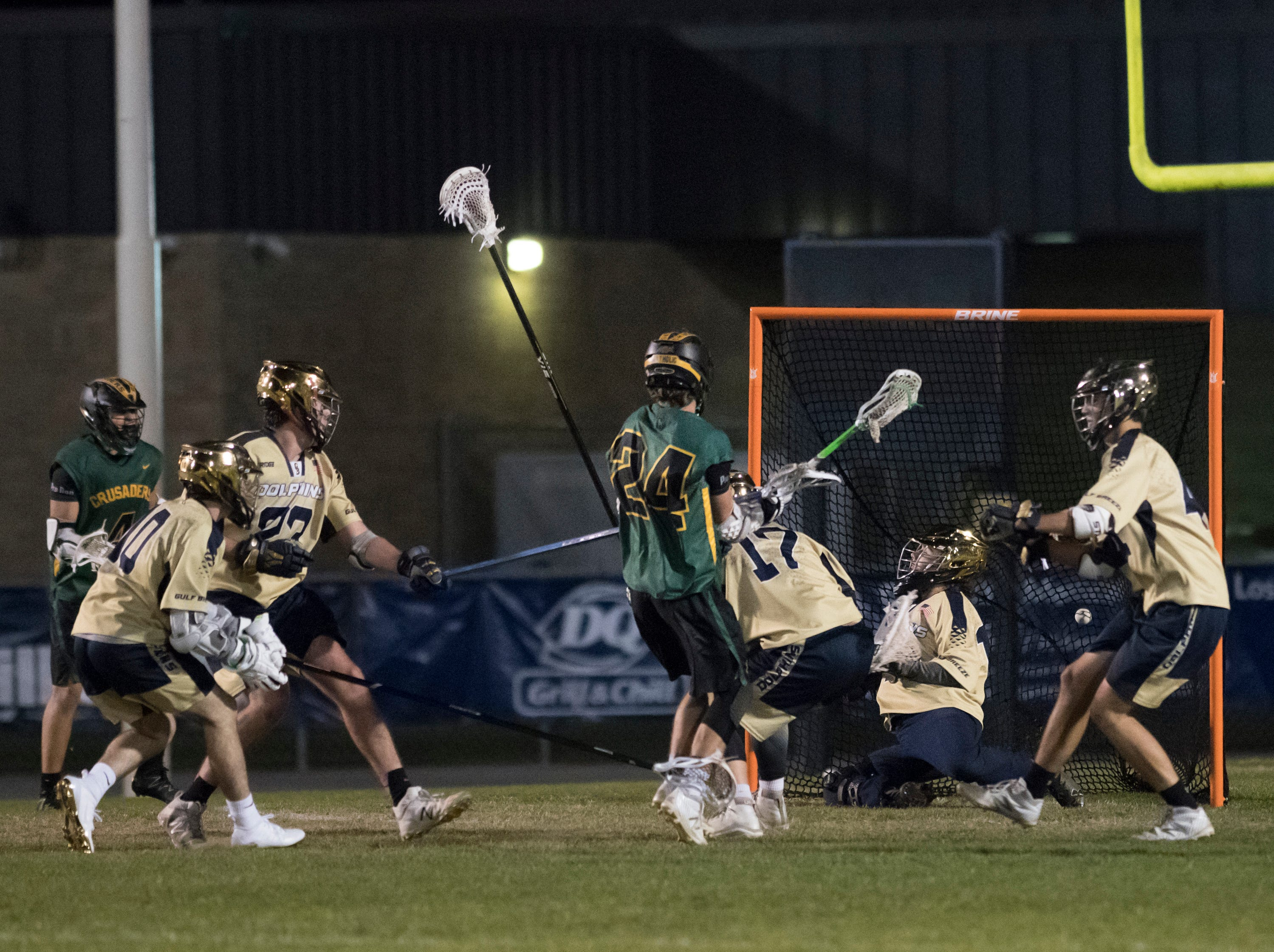 William Butler (24) watches his shot get past goalie Garrison Story (19) as the Crusaders tie the score at 9-9 during the Catholic vs. Gulf Breeze boys lacrosse game at Gulf Breeze High School on Wednesday, March 6, 2019.