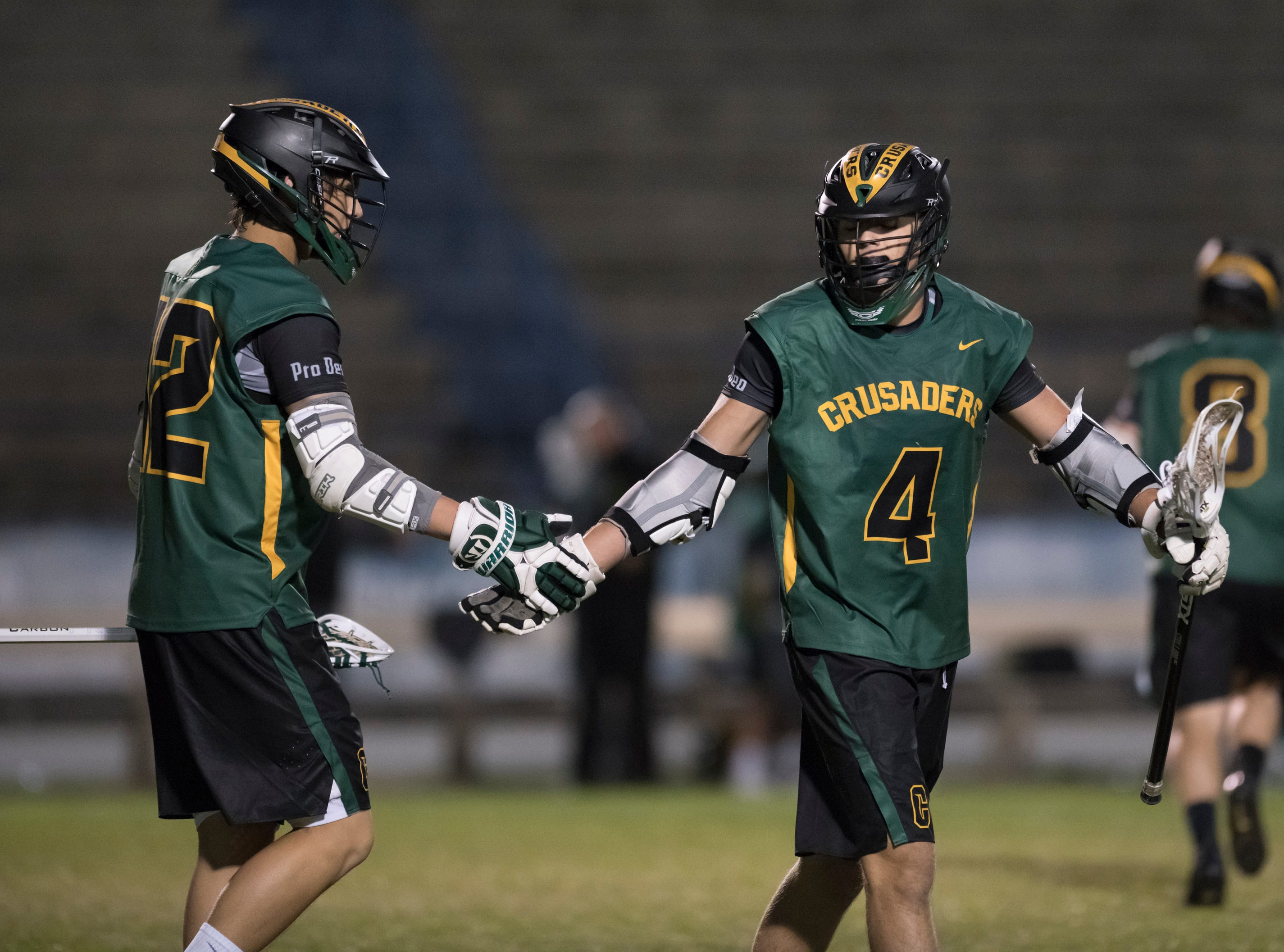 Braeden Lasquety (12) congratulates Bryant Mixon (4) on his goal as the Crusaders take a 5-3 lead during the Catholic vs. Gulf Breeze boys lacrosse game at Gulf Breeze High School on Wednesday, March 6, 2019.