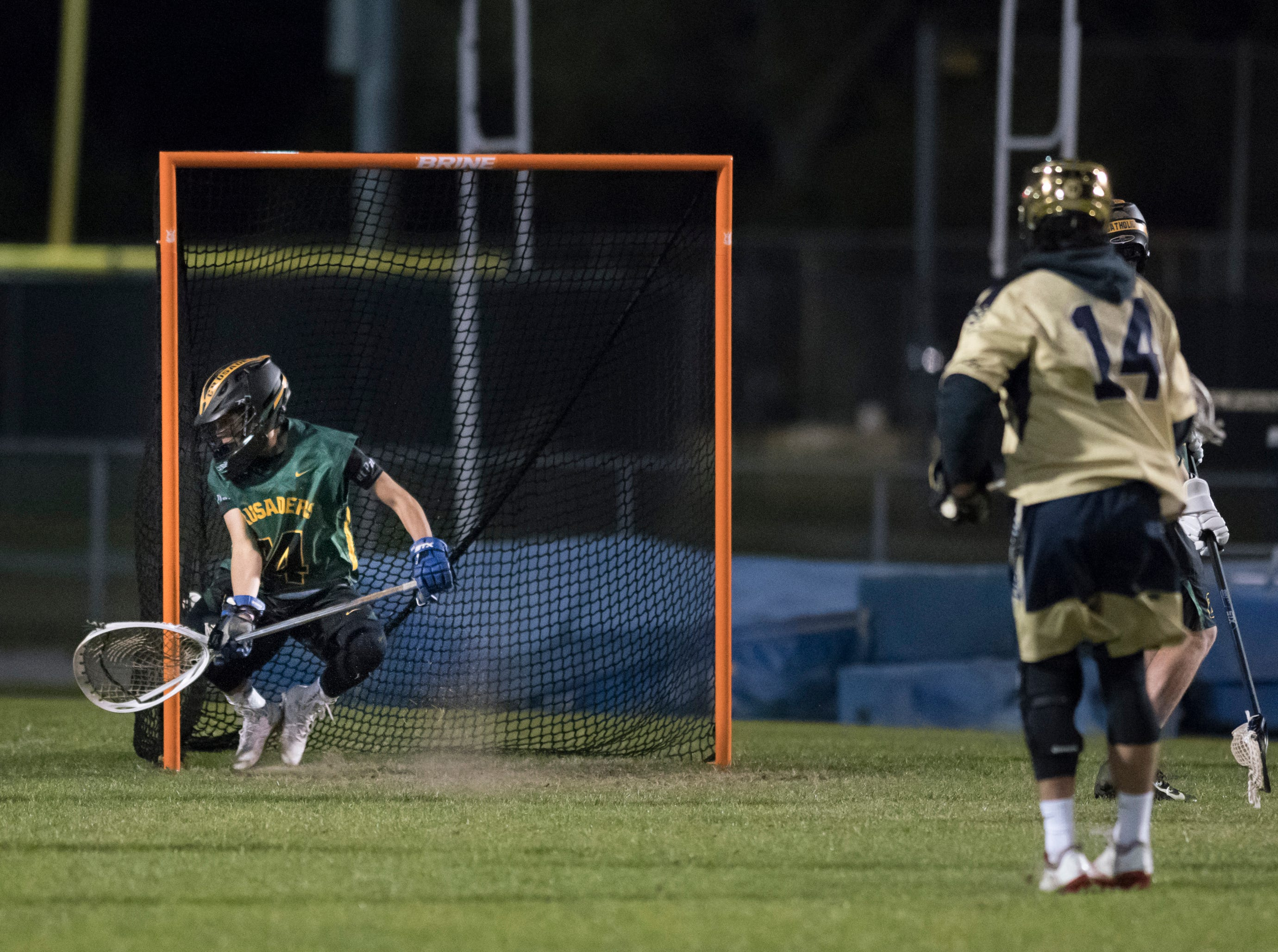 TJ Caldwell (14) watches his shot get past goalie Phillip Garcia (14) as the Dolphins cut the lead to 4-1 during the Catholic vs. Gulf Breeze boys lacrosse game at Gulf Breeze High School on Wednesday, March 6, 2019.