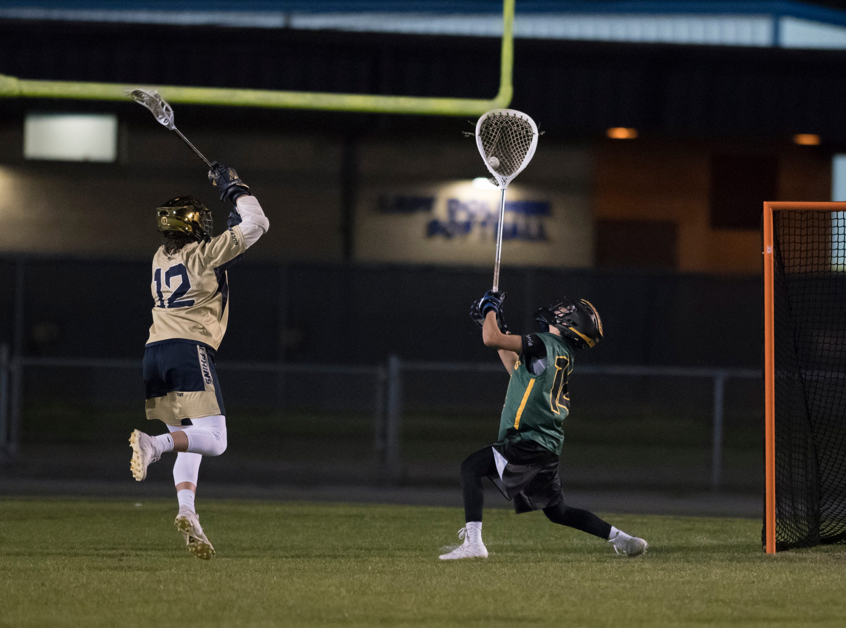 Goalie Phillip Garcia (14) snags Nate Branton (12)'s shot during the Catholic vs. Gulf Breeze boys lacrosse game at Gulf Breeze High School on Wednesday, March 6, 2019.