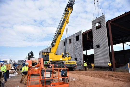 Workers with Conewago Enterprises install exterior panels of what will become a 25,000 square foot simulation of a manufacturing plant, slated to open up to New Oxford students and the community in the fall of 2019.