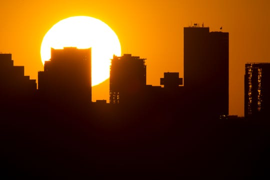 The sun sets behind downtown Phoenix on June 25, 2013.