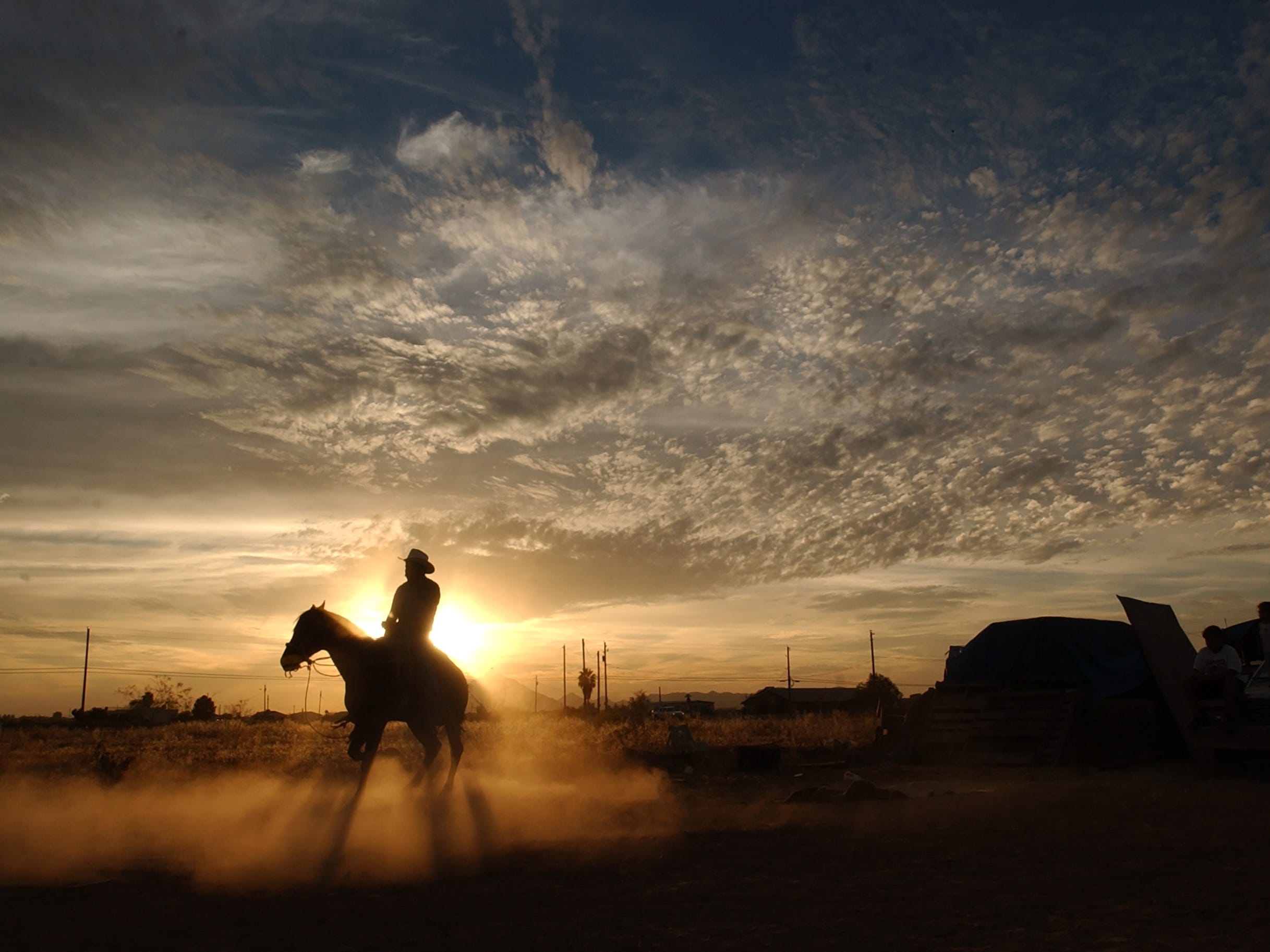 With the sun setting behind him, Pascual Valadez,35, rides his horse Thunderfoot while training him at his brother's home on the Salt River Pima-Maricopa Indian Community Monday May 12th.