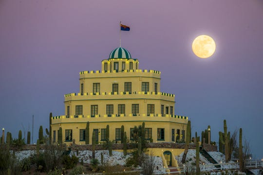 A nearly full moon rises behind Tovrea Castle in Phoenix.