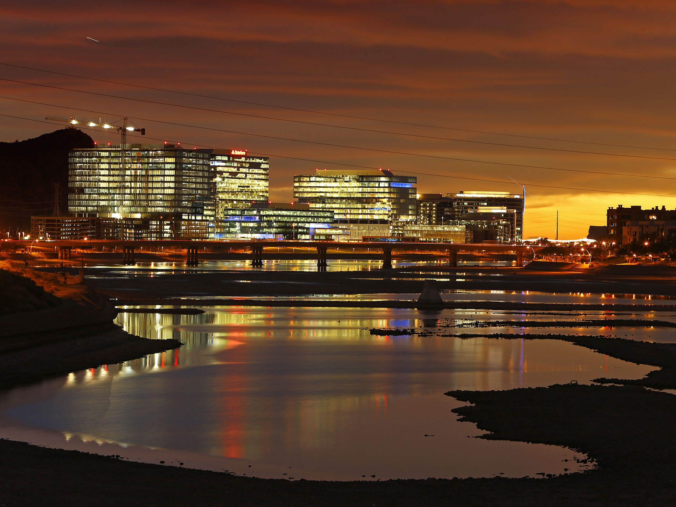 Tempe Town Lake reflects the hues of sunset and lights from high-rises.
