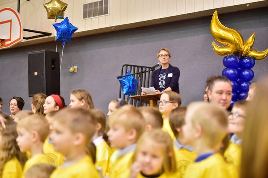 Shalom Christian Academy administrator Angie Petersheim speaks Wednesday, March 6, 2019, at an event to announce a $12 million expansion and renovation project and accompanying Cultivating Wholeness Campaign. Elementary students in yellow T-shirts and several teachers or staff stand in front of her.