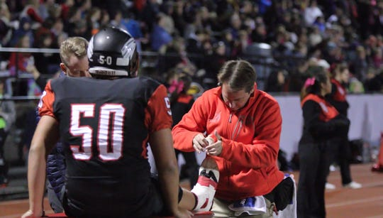 Dover athletic trainer Dave App tapes the ankle of an Eagles lineman.