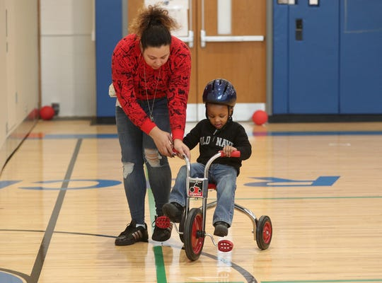 Antoine Howard learns to ride a tricycle with the help of paraprofessional Karina Ramos.