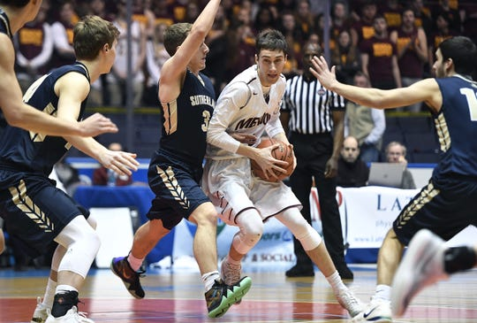 Pittsford Mendon's Connor Krapf, center, is defended by Pittsford Sutherland's John Luther during the Class A state qualifier played at The Blue Cross Arena, Wednesday, March 6, 2019.