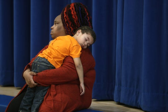 Brian Dixon gets some rest with paraprofessional Georgia Harris during a Pre-K gross motor skills class at School 7.