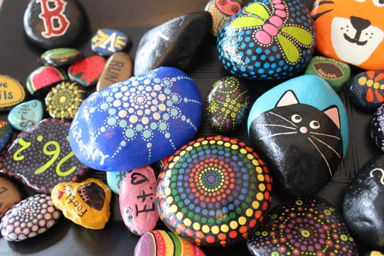Some of the beautifully decorated rocks awaiting placement by Victor residents Dan and Christina Smith and their daughters Danica and Kendall. The Smiths are behind a positive, creative community movement called Victor, NY Rocks.