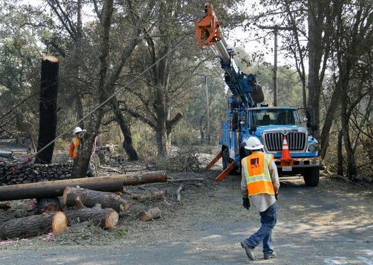 In this Oct. 18, 2017, file photo, a Pacific Gas & Electric crew works on replacing poles destroyed by wildfires in Glen Ellen, Calif. A federal judge said Tuesday he will closely monitor Pacific Gas & Electric's tree-trimming this year and barred the utility from paying out dividends to shareholders as part of a new, court-ordered wildfire prevention plan.