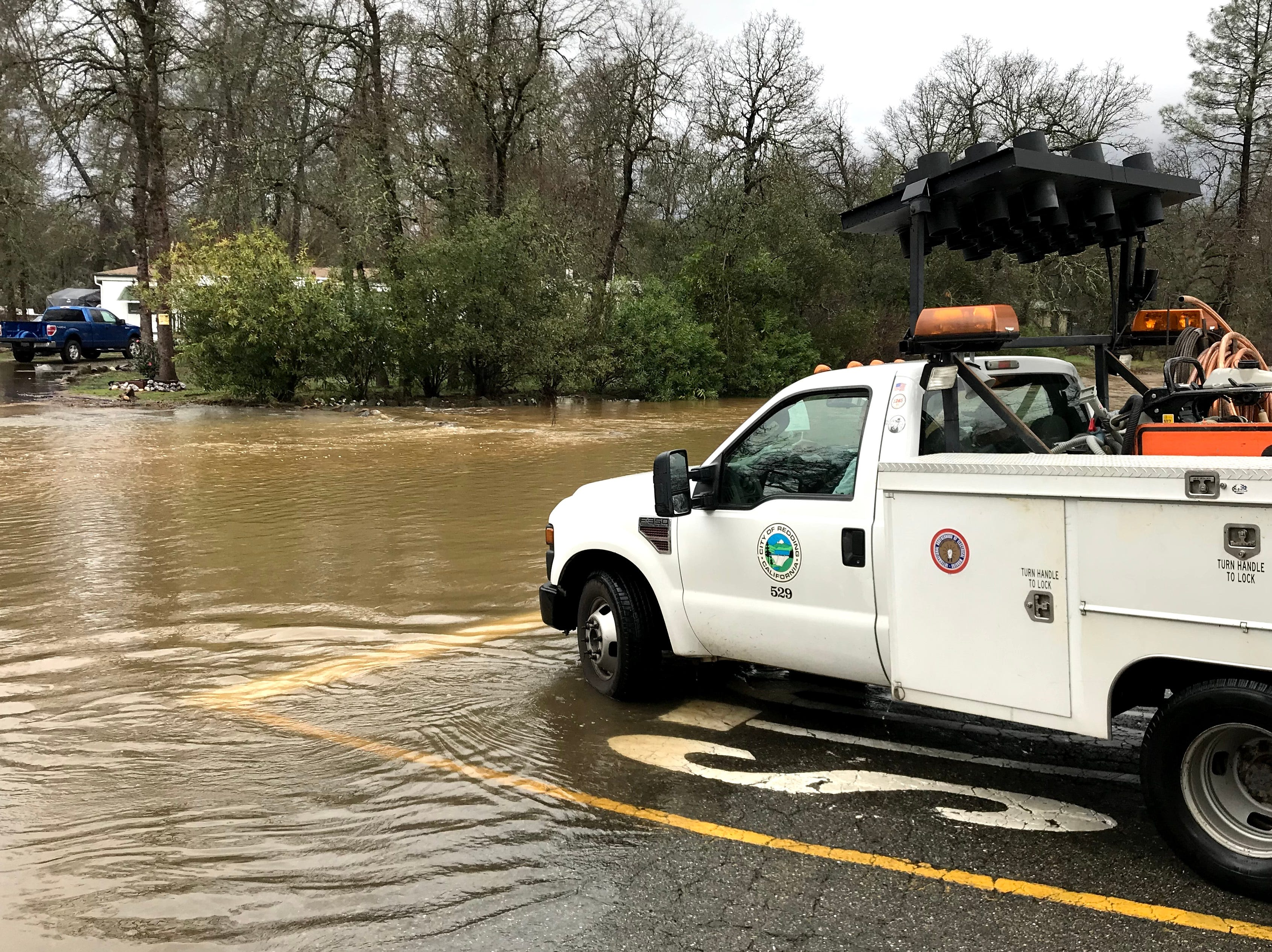 A Shasta County Public Works Department truck stops before entering floodwaters on Old Oasis Road in north Redding.
