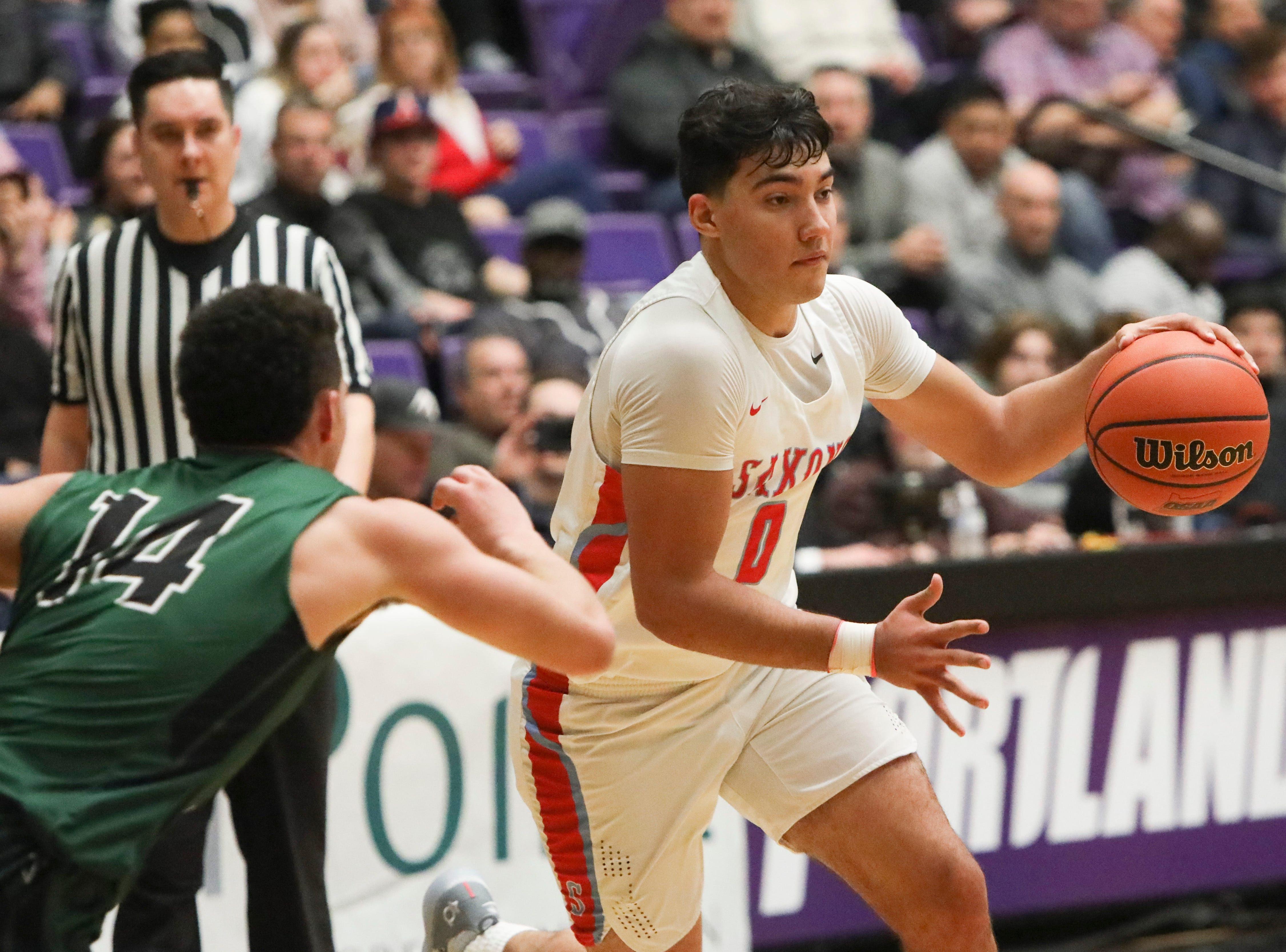 South Salem's Treyden Harris (0) drives past Tigard's Max Lenzy (14) during the OSAA 6A boys basketball state tournament quarterfinal on Wednesday, March 6 at Chiles Center.