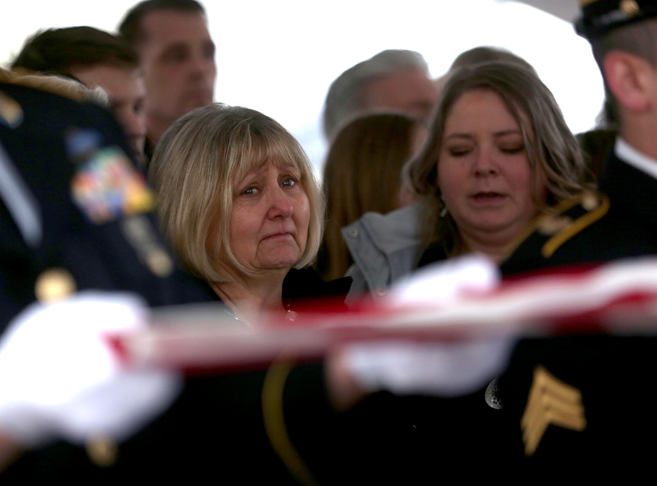Cathy Richardson watches as military members fold the flag during the state funeral for Secretary of State Dennis Richardson at the Oregon State Capitol in Salem on Wednesday, March 6, 2019.