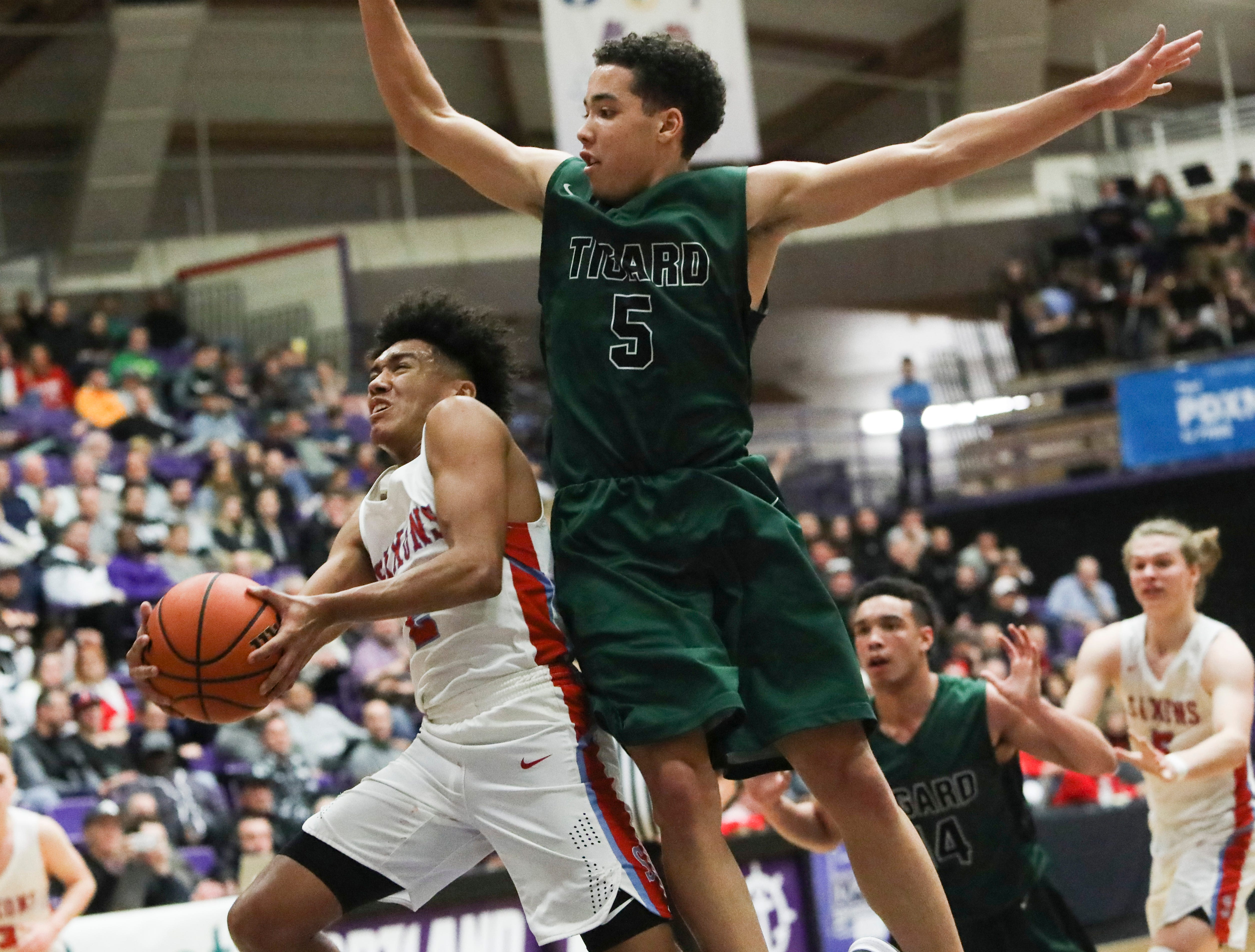 Tigard's Drew Carter (5) tries to block a shot by South Salem's Jaden Nielsen-Skinner (2) during the OSAA 6A boys basketball state tournament quarterfinal on Wednesday, March 6 at Chiles Center.