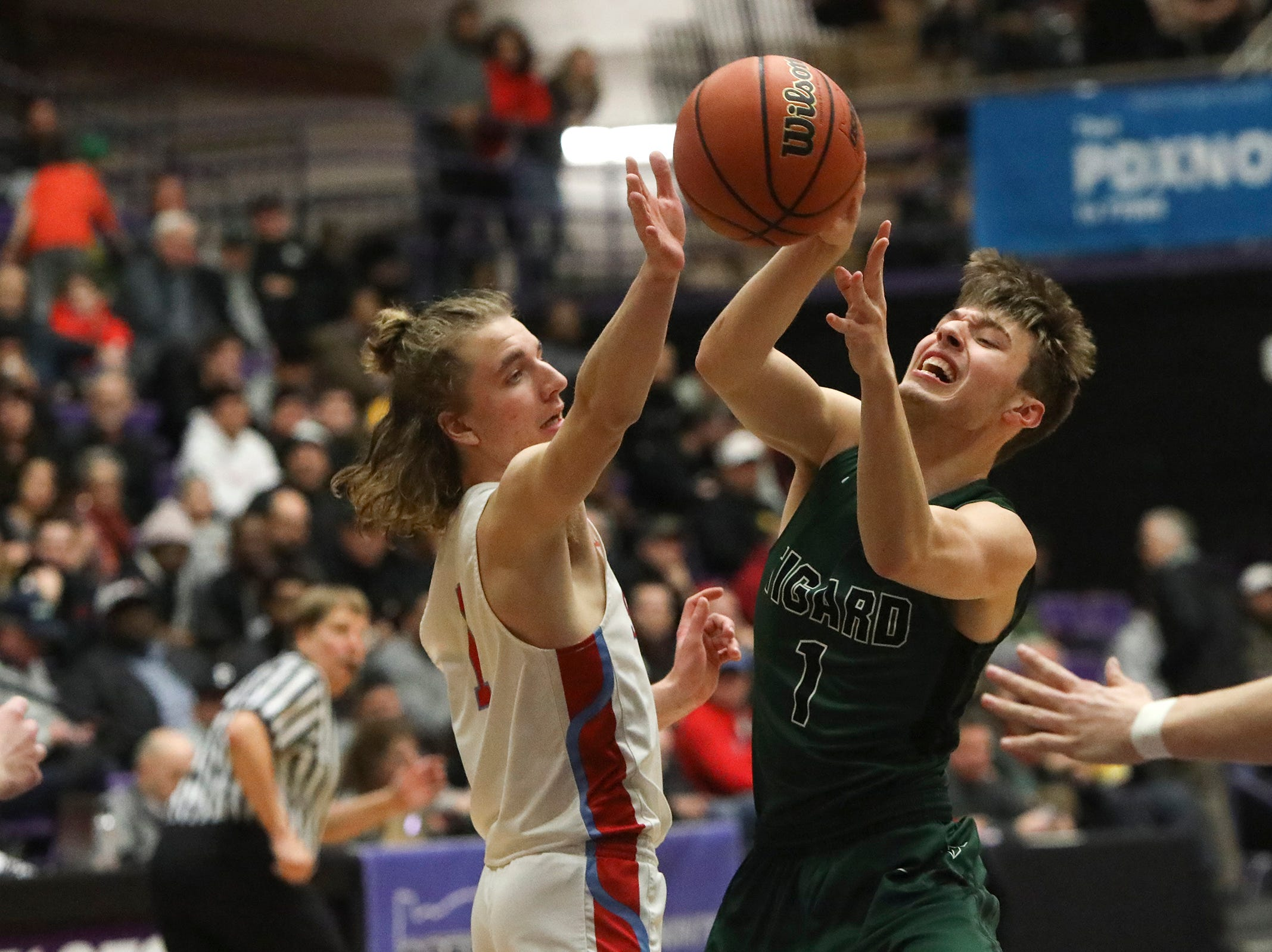 Tigard's Diego Lopez (1) passes over South Salem's Eric Lungu (1) during the OSAA 6A boys basketball state tournament quarterfinal on Wednesday, March 6 at Chiles Center.