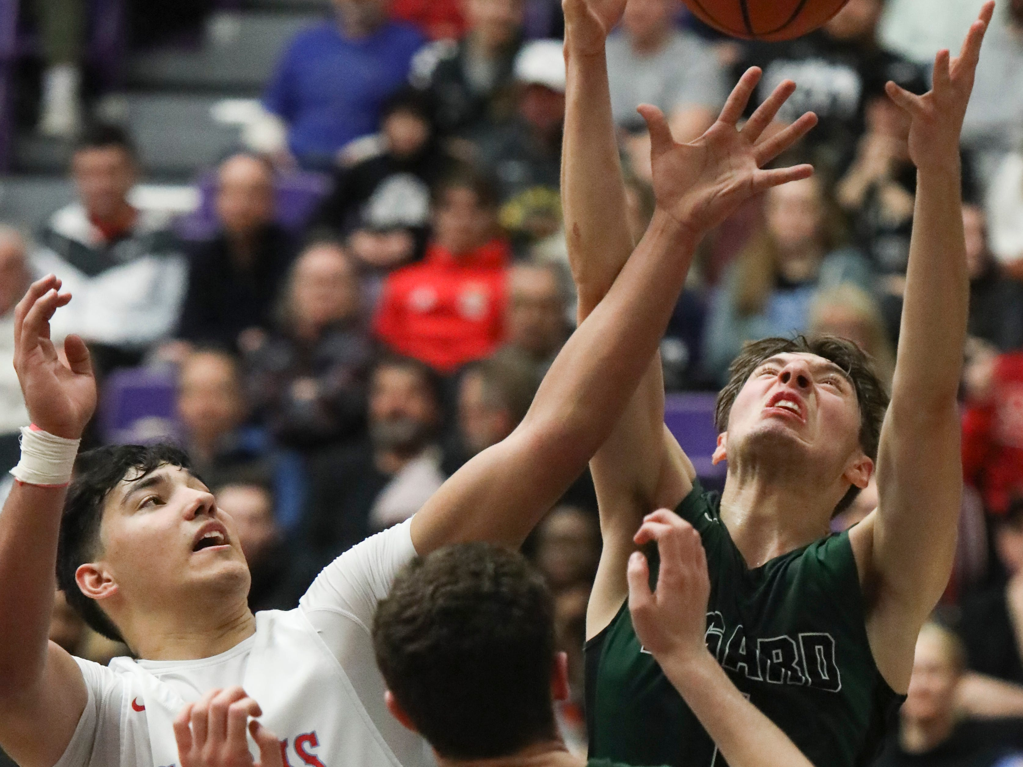 South Salem's Treyden Harris (0) fights for a rebound with Tigard's Luke Ness (20) and Diego Lopez (1) during the OSAA 6A boys basketball state tournament quarterfinal on Wednesday, March 6 at Chiles Center.