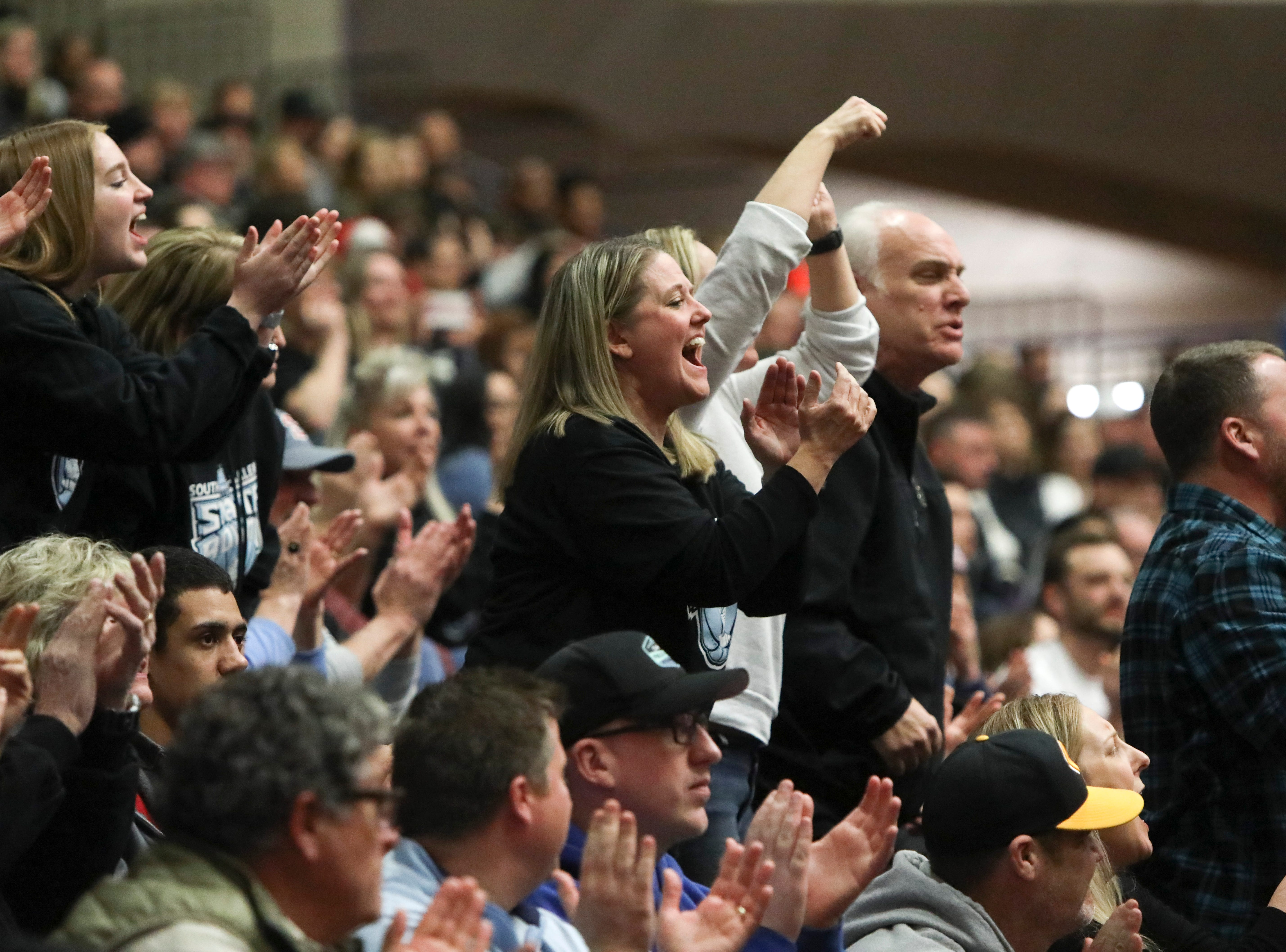 The South Salem fan section celebrates a basket during the OSAA 6A boys basketball state tournament quarterfinal against Tigard on Wednesday, March 6 at Chiles Center.