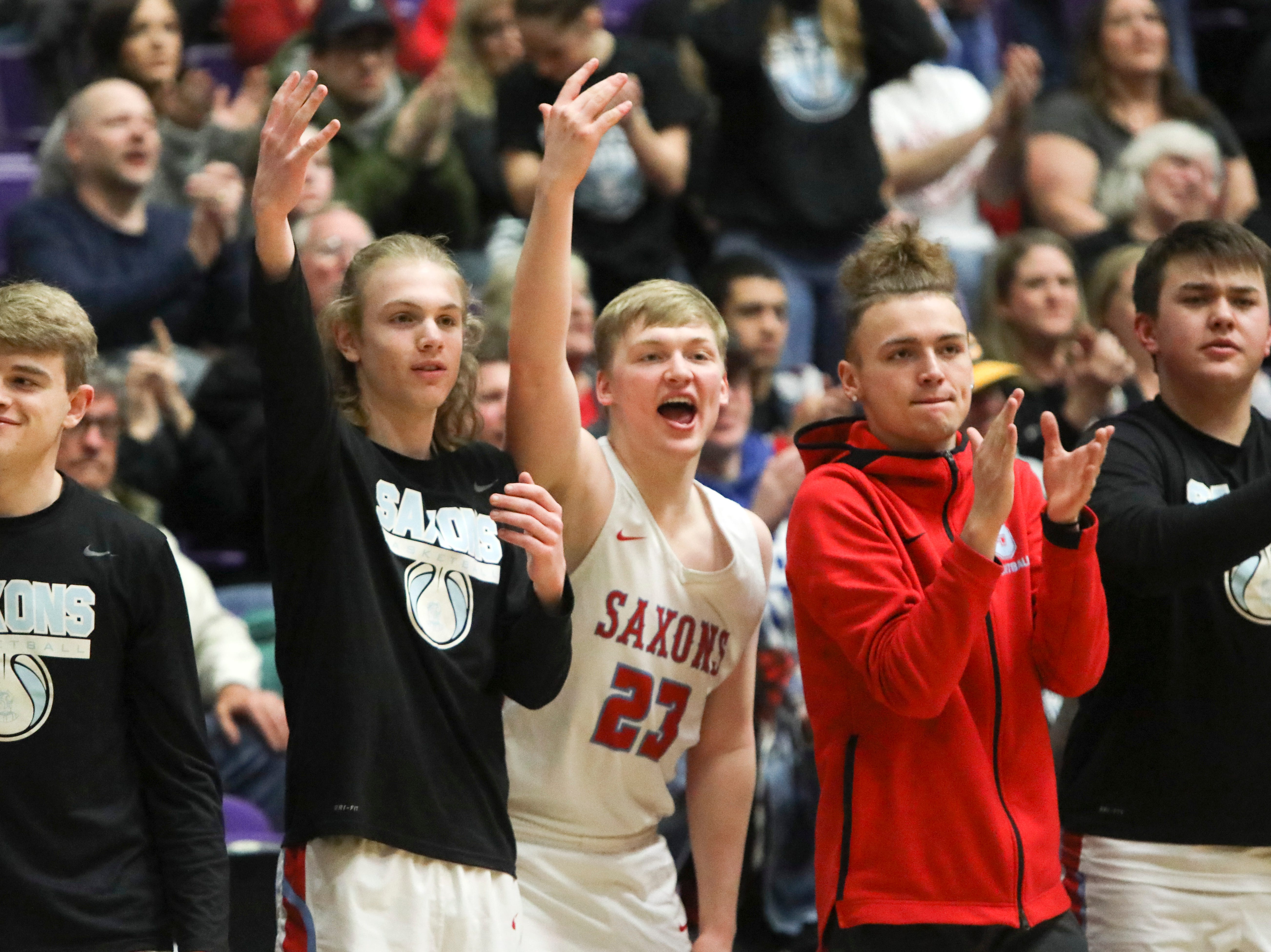 The South Salem bench celebrates a basket against Tigard during the OSAA 6A boys basketball state tournament quarterfinal against Tigard on Wednesday, March 6 at Chiles Center.
